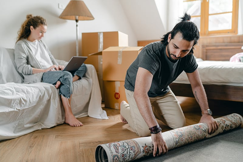 Eine Frau sitzt auf der Couch, während ein Mann einen Teppich in eine Wohnung legt
