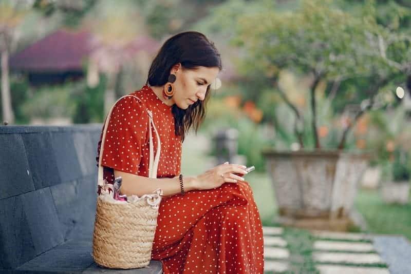 Eine Frau sitzt auf einer Bank und benutzt ein Handy