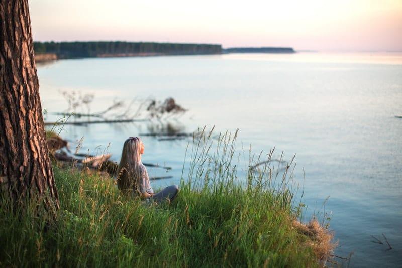 Eine Frau sitzt im Gras und schaut auf das Meer