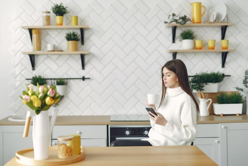 Eine Frau sitzt in der Küche und benutzt ein Handy beim Kaffee