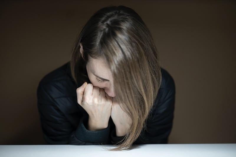 Eine Frau lehnte ihren Kopf an die Fäuste, während sie am Tisch saß