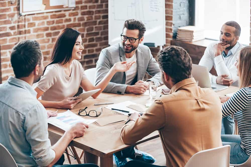 Eine Geschäftsfrau am Tisch sitzt und erklärt der Gruppe etwas