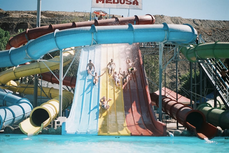 Eine Gruppe von Menschen rutscht auf der Poolrutsche im Wasserpark