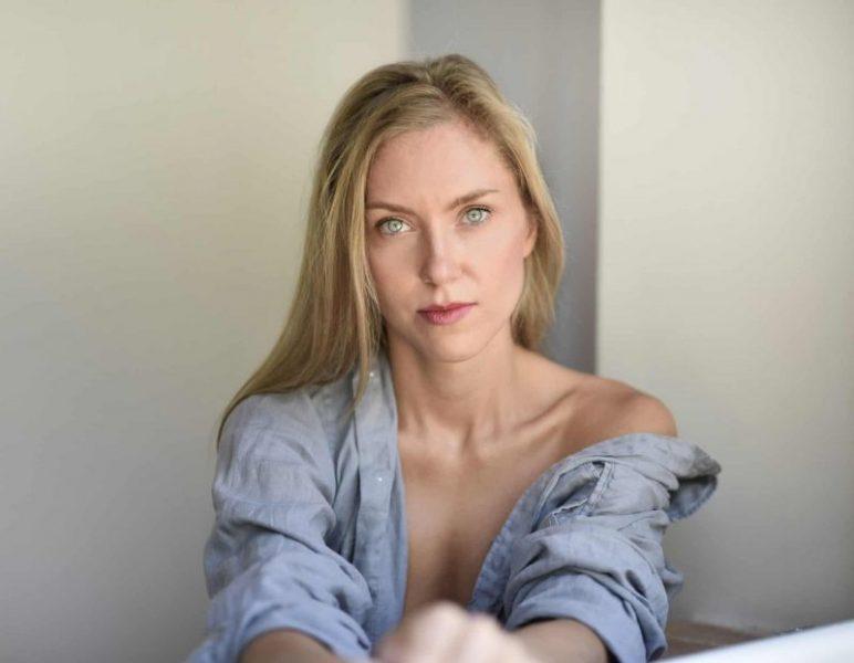 Eine ernsthafte Blondine sitzt in einem Jeanshemd für Männer