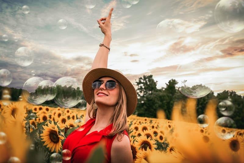 Eine glückliche Frau in einem roten Kleid mit Sonnenschirmen steht in einem Feld von Sonnenblumen