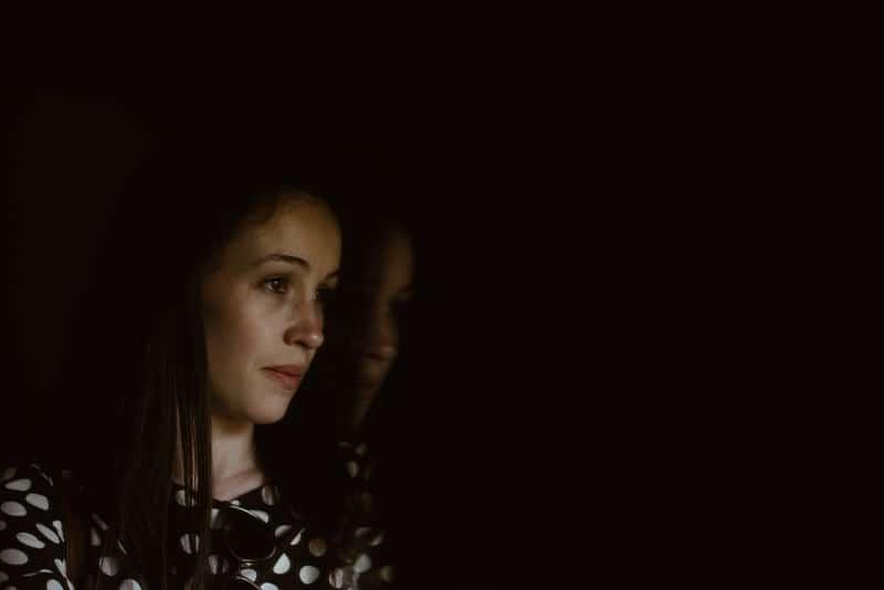 Eine jüngere Frau in einem gepunkteten Hemd steht traurig da