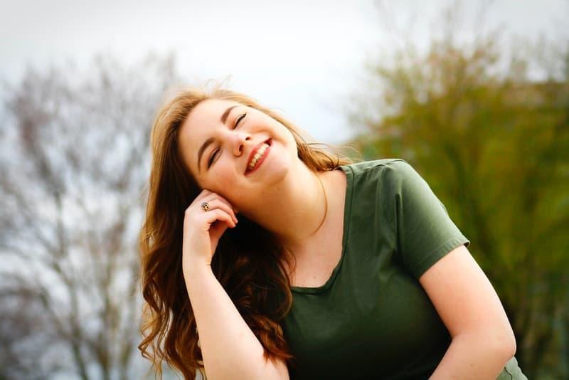 Eine lächelnde rothaarige Frau in einem grünen T-Shirt sitzt im Park