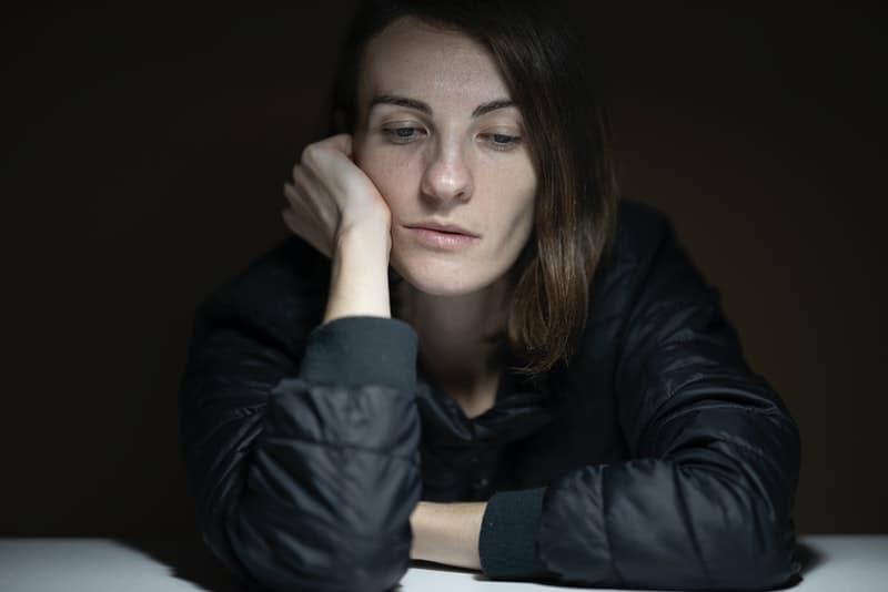 Eine obsessiv nachdenkliche Frau sitzt traurig