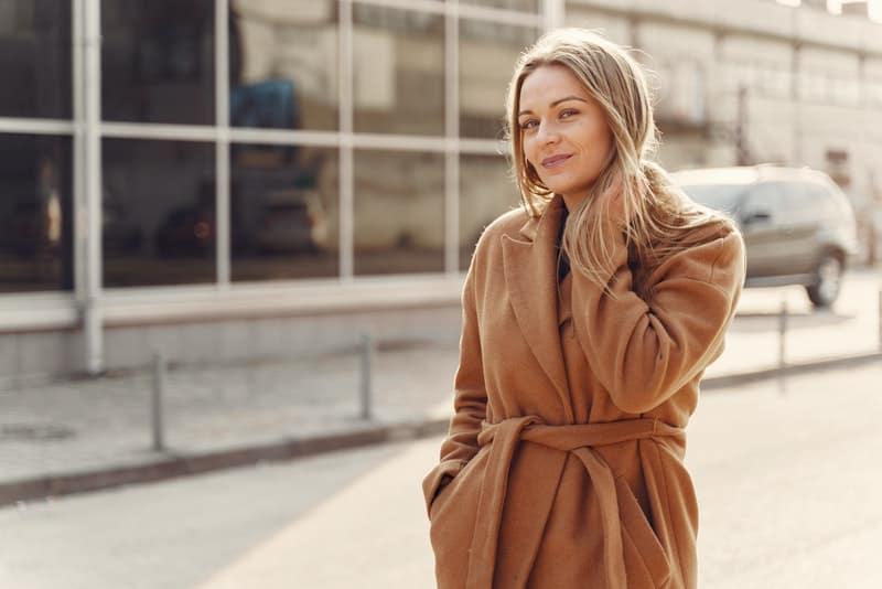 Eine schöne Blondine in einem braunen Mantel geht die Straße entlang