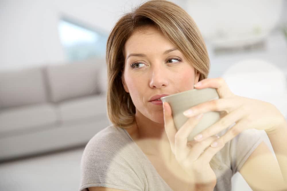 Eine schöne Frau sitzt im Haus und trinkt Tee