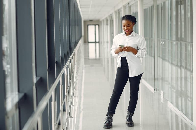 Eine schwarze Frau in einem weißen Hemd schreibt eine SMS