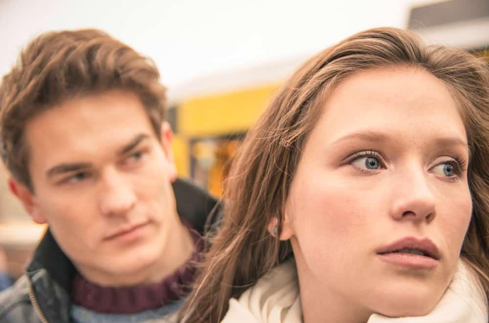 Eine wütende blauäugige Frau ignoriert den besorgten Mann