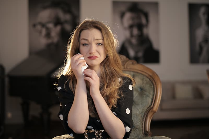 Eine weinende Frau wischt sich mit einem Taschentuch die Tränen ab, während sie auf dem Stuhl im Raum sitzt