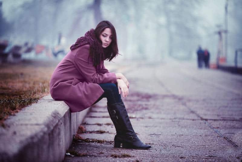 Enttäuschende junge Frau sitzt an diesem Herbsttag auf der Steinbrüstung