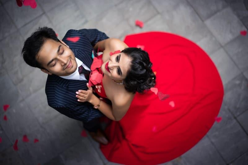 Ein Mann in einem formellen Anzug und eine Frau in einem roten Kleid tanzen auf der Straße