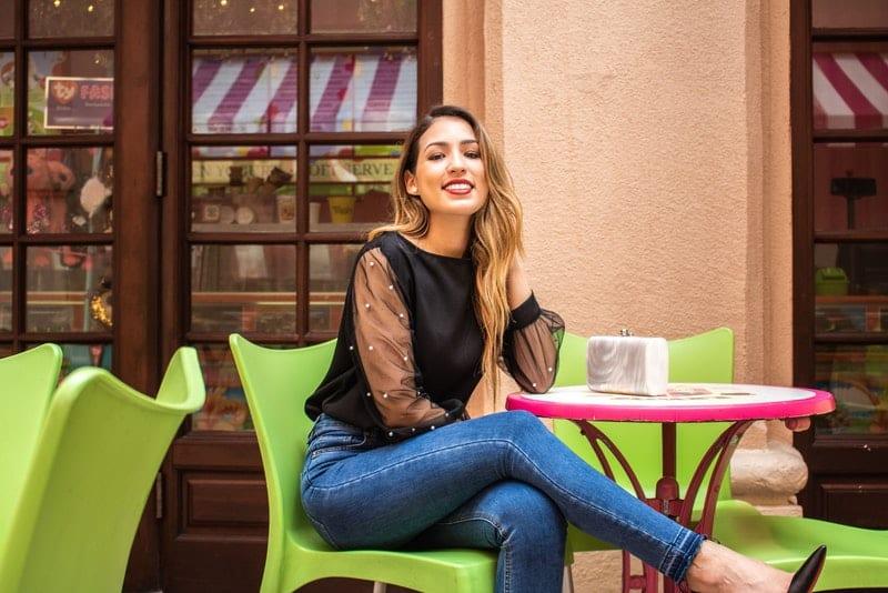 Eine attraktive Frau mit langen, gutaussehenden Beinen sitzt lächelnd auf der Terrasse eines Cafés