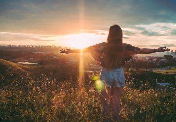 Eine Frau in kurzen Hosen steht mit ausgestreckten Armen bei Sonnenuntergang auf einem Hügel