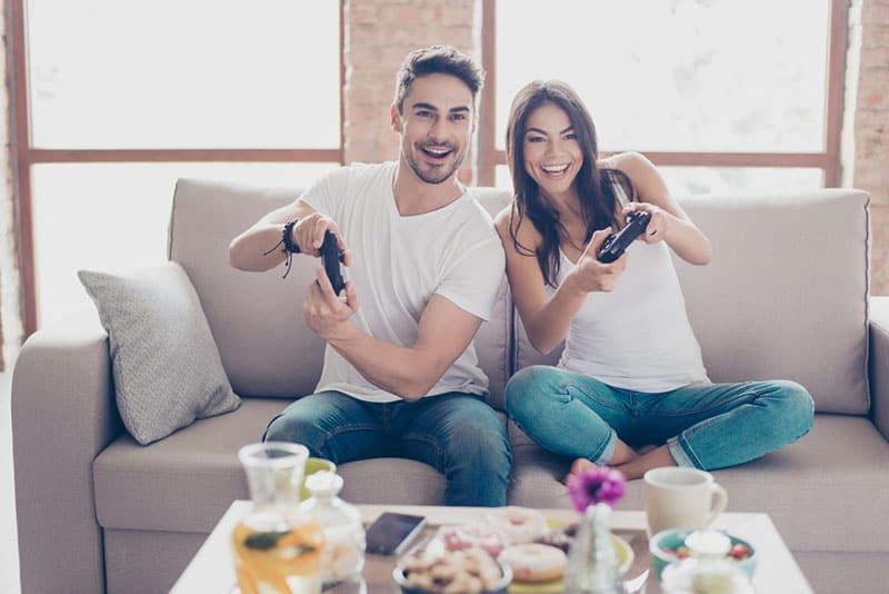 Mann und Frau spielen mit Playstation