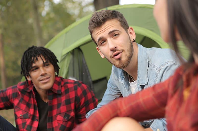 zwei Männer sprechen mit einem Mädchen, während sie in der Natur auf dem Campus sitzen
