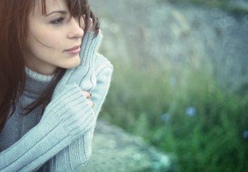 ein depressives Mädchen sitzt neben einer Wiese