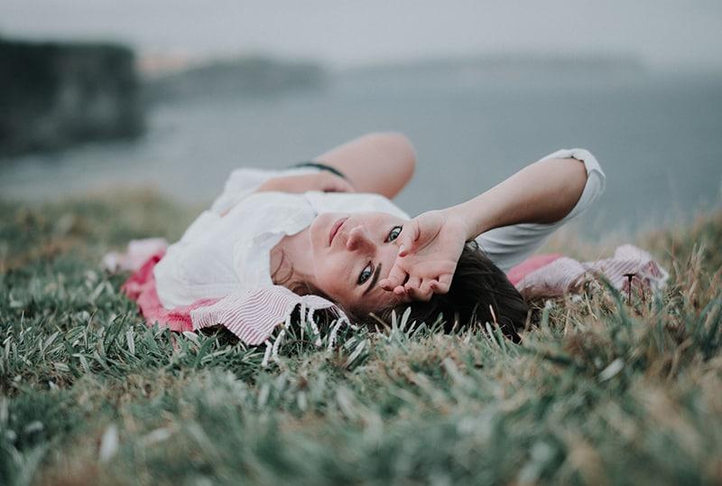 Die Frau liegt im grünen Gras und hält ihre Hand am Baum
