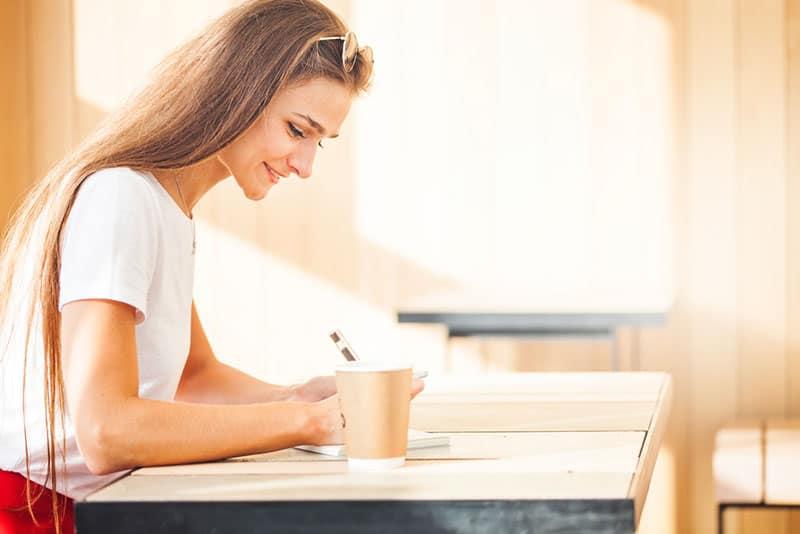 Frau, die einen Brief im Café schreibt
