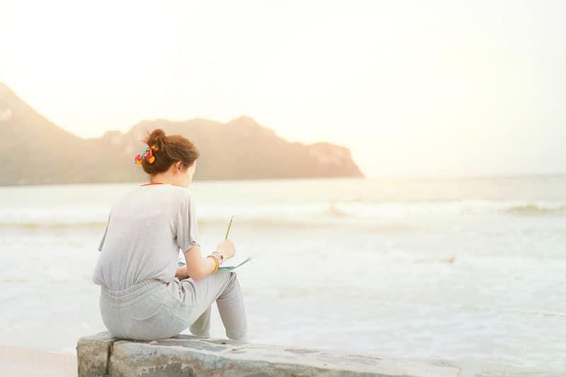 Frau schreibt einen Brief am Meer
