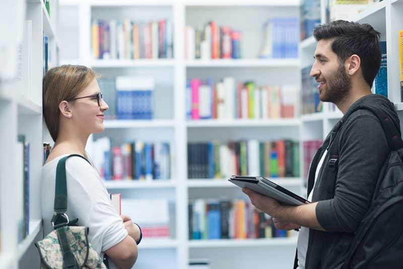 Frau und Mann schauen sich in der Bibliothek an