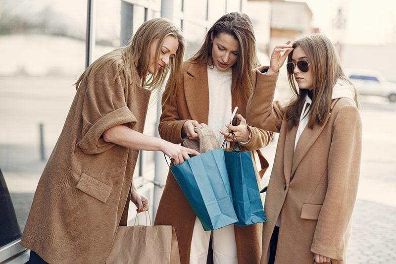 Frauen untersuchen neuen Pullover in Einkaufstasche, während sie auf dem Bürgersteig stehen