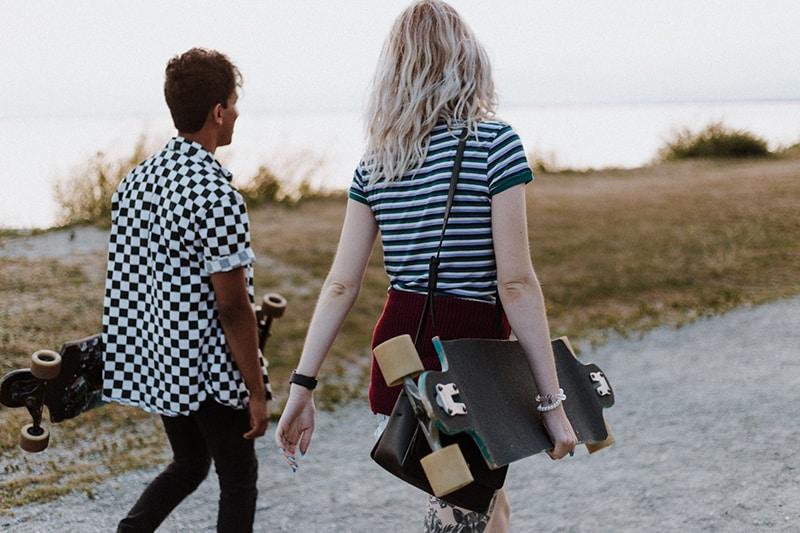 Freunde gehen zusammen auf der Straße mit Skateboard in den Händen