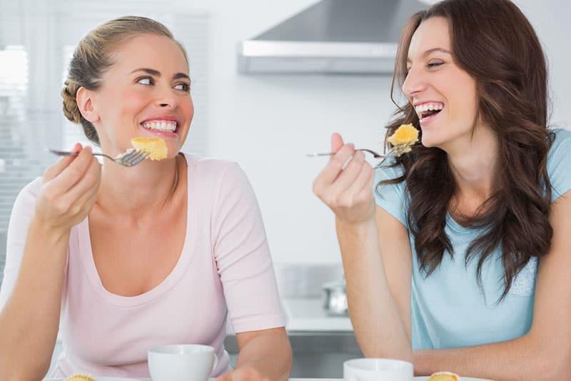 Freunde lachen und Kuchen essen
