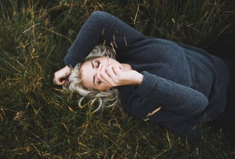 eine Blondine, die im Gras liegt