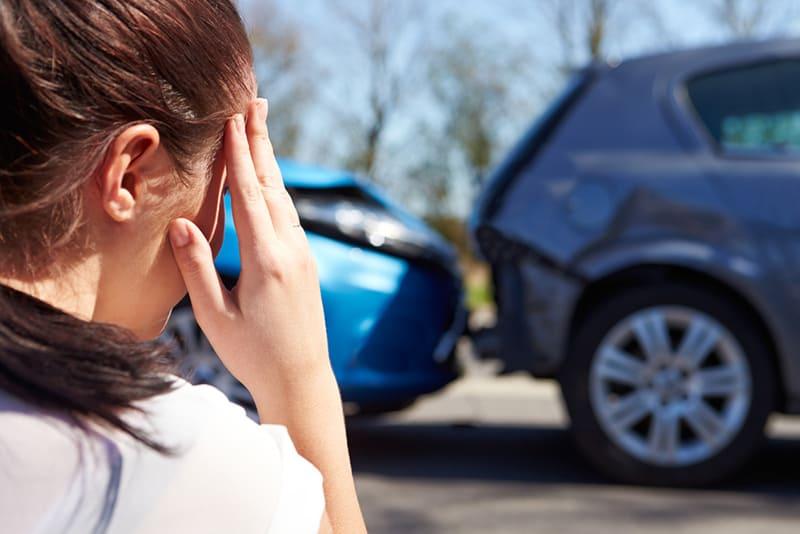 Gestresster Fahrer, der nach Verkehrsunfall am Straßenrand sitzt