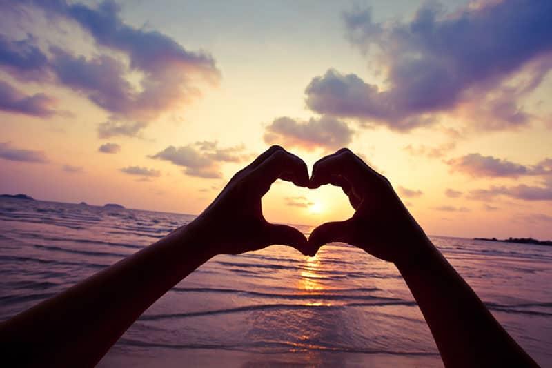 Herz aus Händen bei Sonnenuntergang