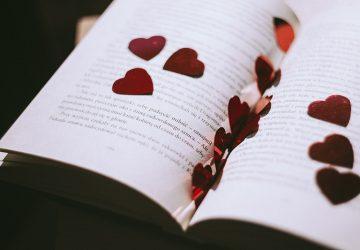 rotes herzförmiges Konfetti auf dem geöffneten Buch