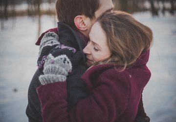 eine Frau, die einen Mann umarmt, während sie auf dem Schnee steht