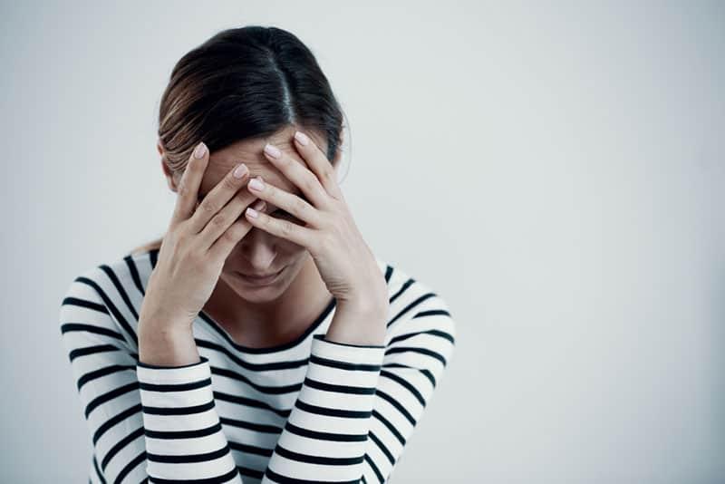 depressive Frau mit Händen im Gesicht