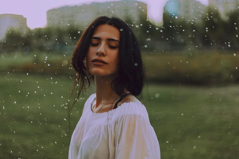 eine kindische Frau, die mit geschlossenen Augen auf dem Regen steht