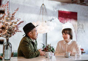 Ein Mann spricht mit einer Frau in einem Café, während er mit den Händen gestikuliert