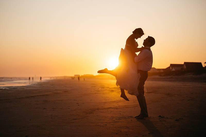 Mann, der Frau während des Sonnenuntergangs hält