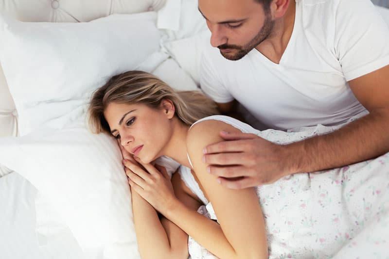 Mann, der Hand auf Frau Schulter im Bett hält