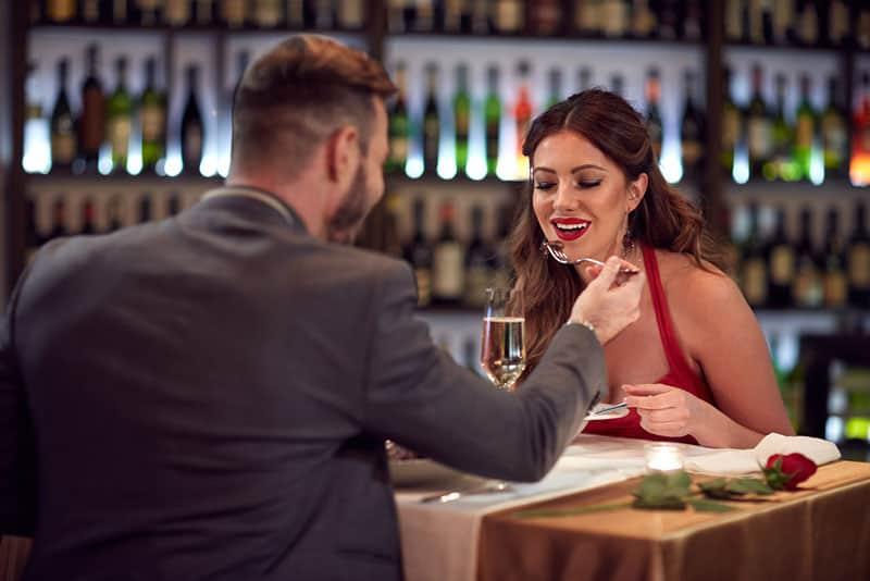 Mann füttert Frau im Restaurant