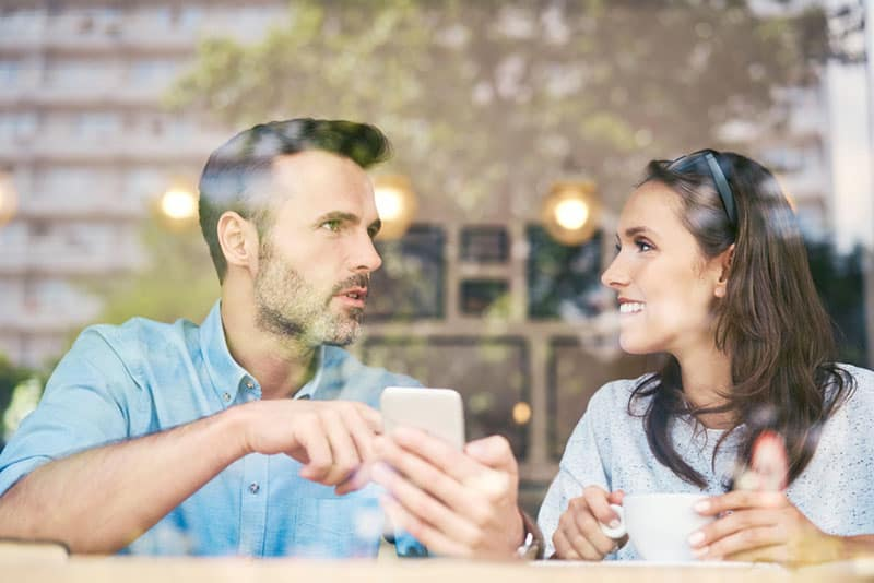 Mann hält Telefon und spricht mit Frau