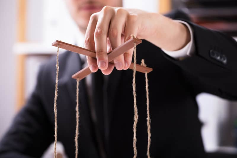Mann hält manipulierende Marionettenschnur