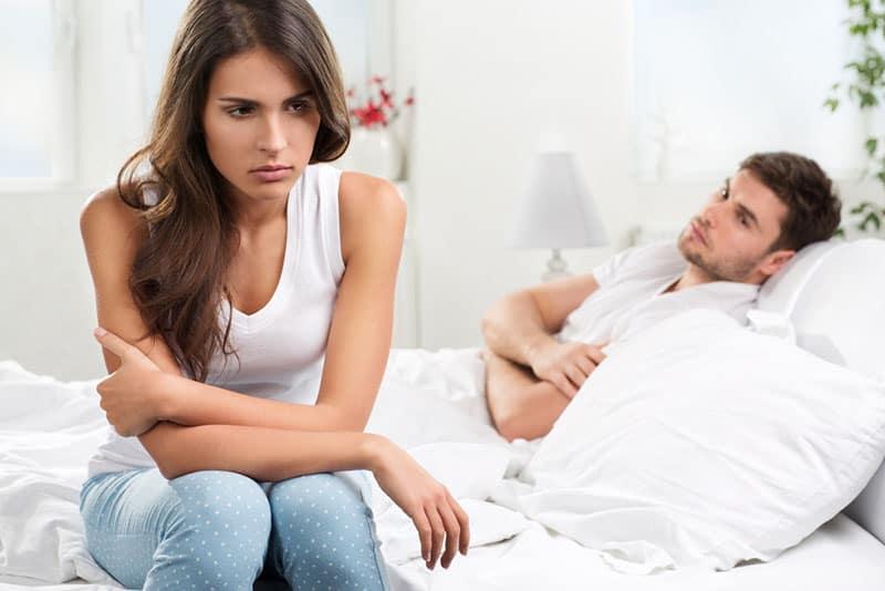 Mann im Bett liegend, während Frau distanziert