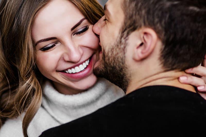 Mann küsst lächelnde Frau