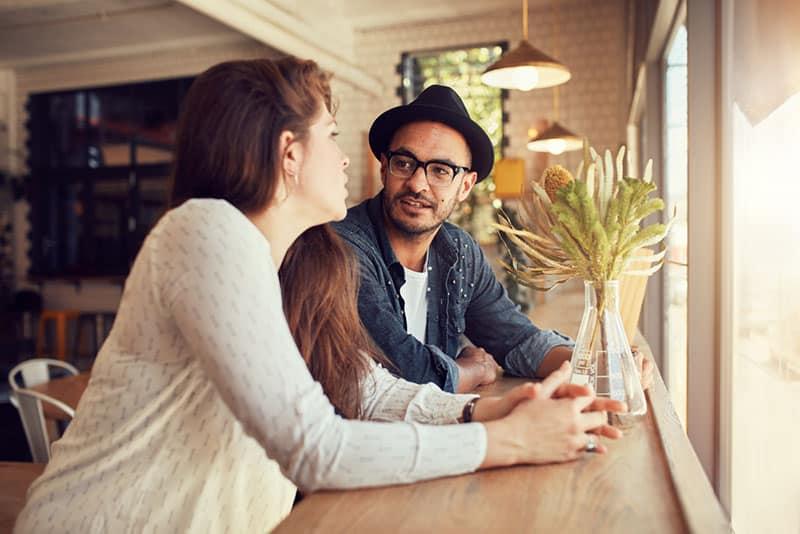 Mann mit Hut im Gespräch mit Frau im Café