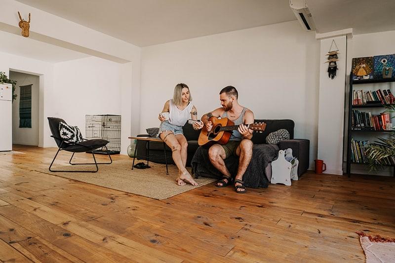 Mann, der akustische Gitarre nahe der Frau spielt, während er im Wohnzimmer sitzt