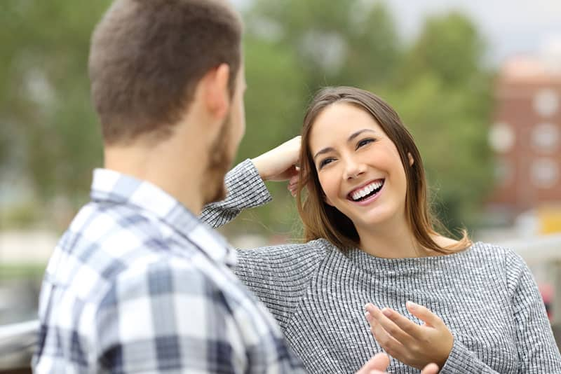 Mann spricht mit lächelnder Frau