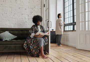 Eine Frau sitzt auf einer Couch, während ein Mann im anderen Raum neben dem Fenster steht
